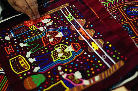 Mola que representa la fiesta por la primera menstruación de una de las mujeres de la comunidad. En la tela se plasma el consumo de chicha.